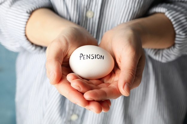 Woman holds egg with inscription pension