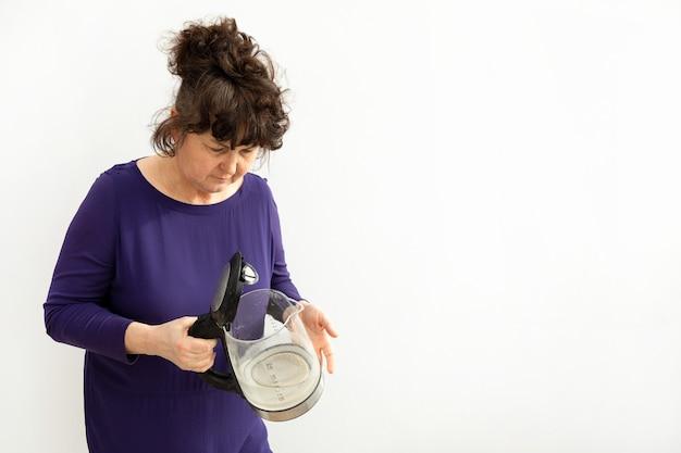 女性は手に水垢が付いた電気ケトルを持っています。炭酸カルシウムのチョーク残留物。硬水による家電修理。