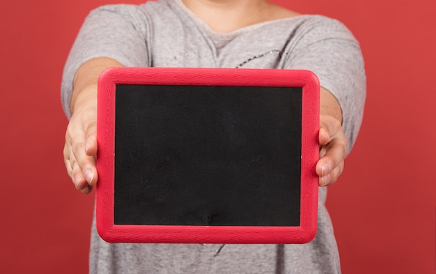 Woman holds empty  frame on red background