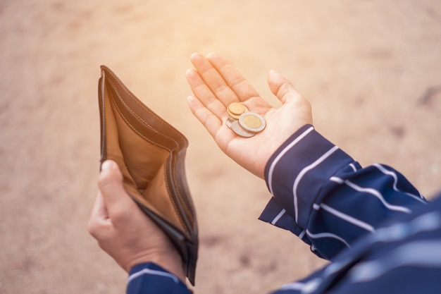 Woman holds an empty purse and coins in hand meaning money financial problem or bankrupt jobless, broke after credit card payday jobless.