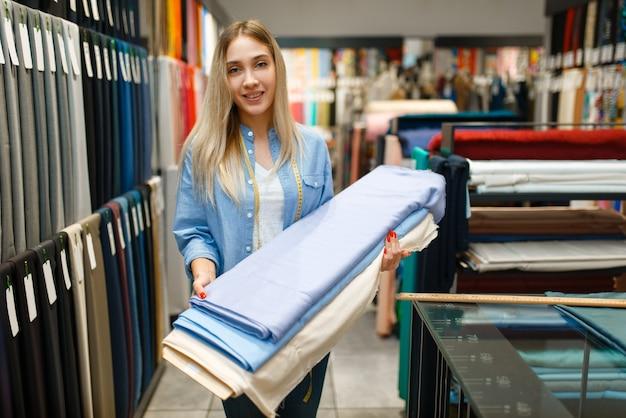Женщина держит ткань в текстильном магазине. полка с тканью для шитья, швея