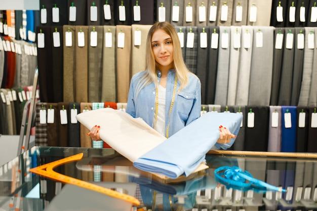 女性は織物店で生地を保持しています。
