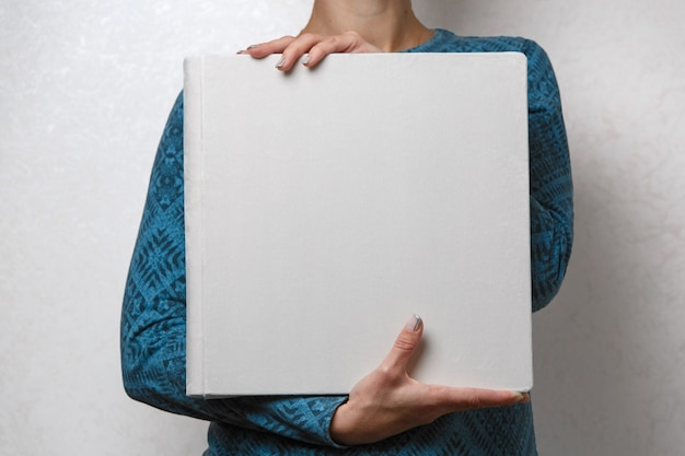 A woman holds a family photobook the person looks at the photo book sample  beige photo album  wedding photoalbum with  fabric cover. female hands holding square photo album.