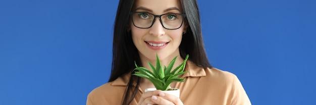 Женщина держит в руках горшок с растением