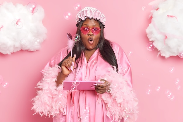 Woman holds folded with papers and pen wears bath hat dressing gown heart shaped sunglasses isolated on pink