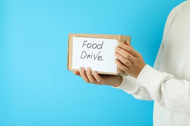 Женщина держит коробку с едой на синем фоне