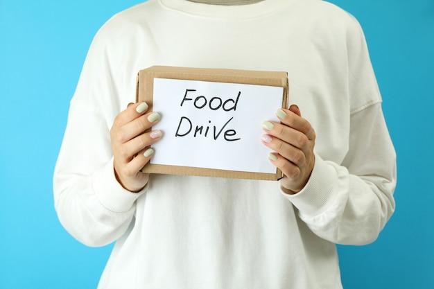 Женщина держит коробку привода еды на синем фоне