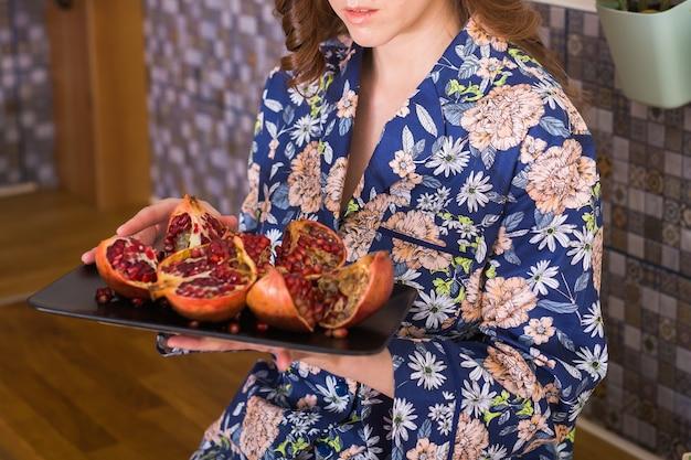 女性は新鮮な熟したザクロを保持しています。果物、ビタミン、食品のコンセプト。閉じる。