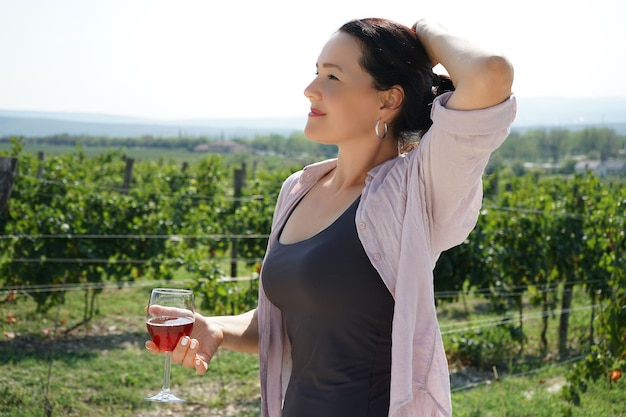 A woman holds a glass, tasting wine in the vineyard during the harvest