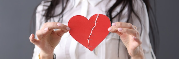 Woman holds glued heart in her hands. love relationship concept