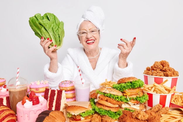 Woman holds green vegetable prefers eating healthy food instead of cheat meal sits at table wears transparent glasses bathrobe and towel on head surrounded by high calorie products