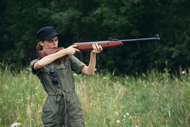 Woman holds guns in front of him aiming side view weapons forest background