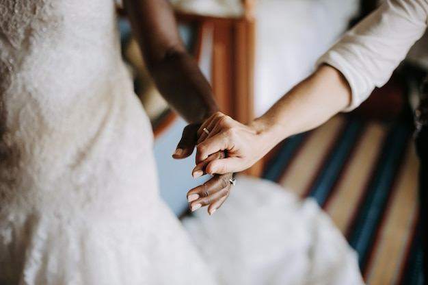 Woman holds hand of african american bride