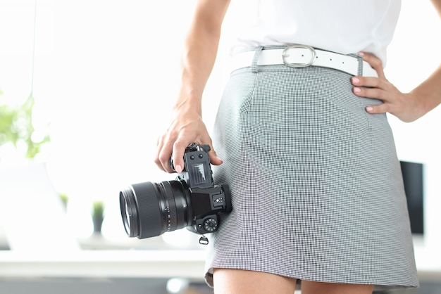 Woman holds in hand black modern photo camera professions related to photography concept