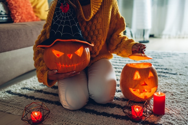 Woman holds hand-made carved pumpkin and opens another one