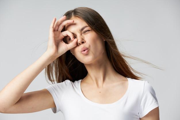 Женщина держит руку возле лица эмоции закрытыми глазами белая футболка