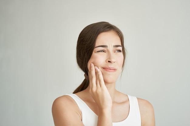 Женщина держит руку на лице, зубы, боль, стоматология, медицина, дискомфорт
