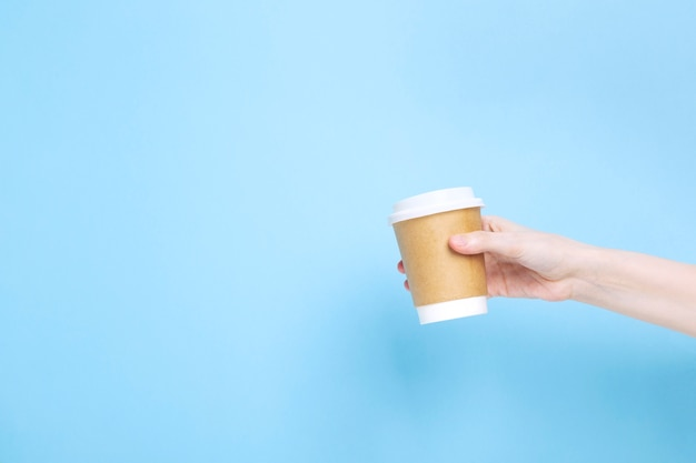 Woman holds hand paper cup with coffee on blue background. copy space