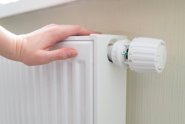 Woman holds hand on the radiator