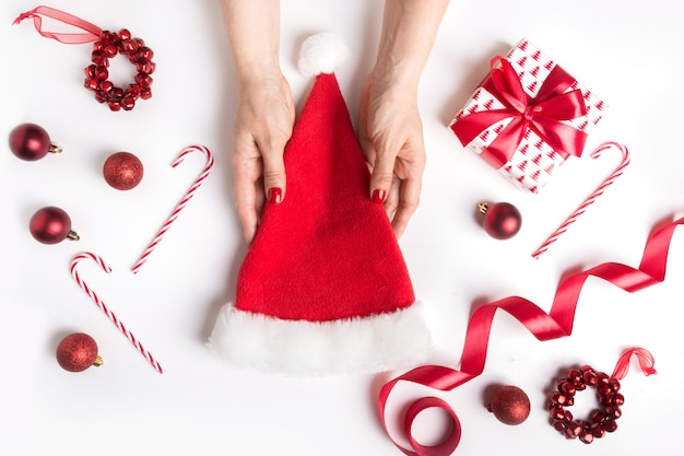 Woman holds in hand santa claus hat on christmas background with red decor.