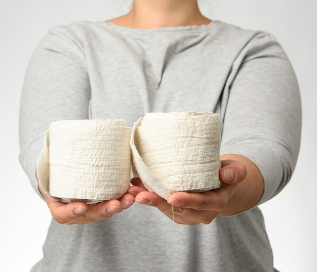Woman holds in hand a white elastic bandage for the body, gray background