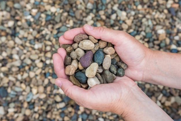 A woman holds a handful of sea pebbles on a beach near the sea