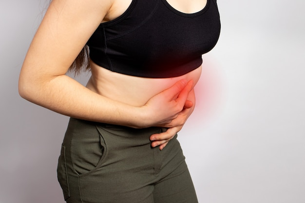 A woman holds hands on a sick stomach with a ulcer or gastritis.