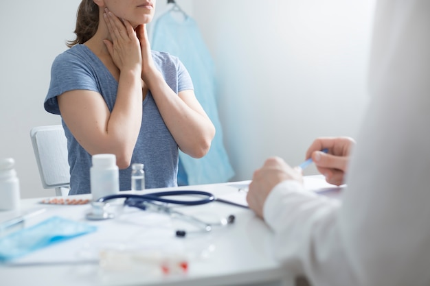 Woman holds hands to sore throat while sitting at a doctor's consultation.