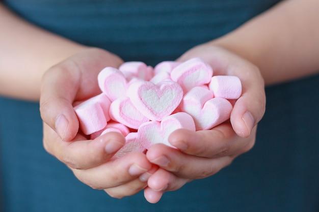 女性はバレンタインデーのためにハート型のマシュマロを保持します