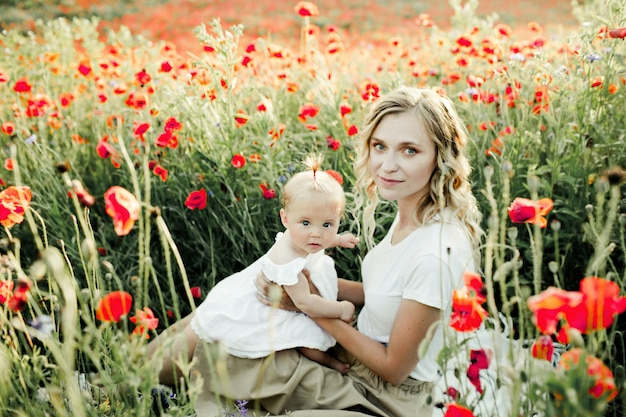 Woman holds her baby among poppy field