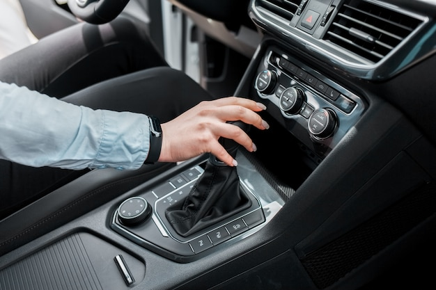 Woman holds her hand on the gear selector automatic transmission