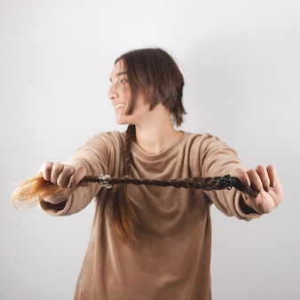 A woman holds in her hand her cut braid of hair she cuts herself.