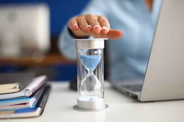 Woman holds her hand over hourglass at workplace in office closeup
