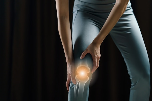 Woman holds her hands to the knee, pain in the knee highlighted in red, medicine, massage concept.