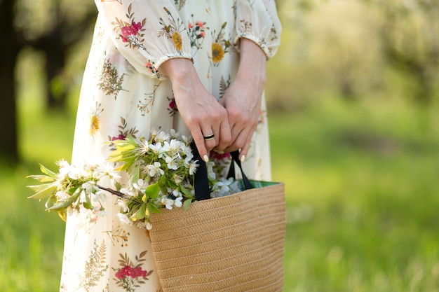 A woman holds in her hands a stylish wicker bag with blooming flowers in green park. spring romantic mood and beuaty of nature