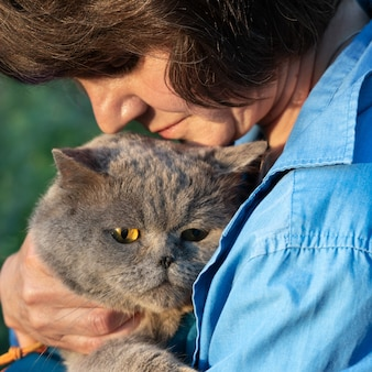 Woman holds her lovely british short hair cat outddors in summer
