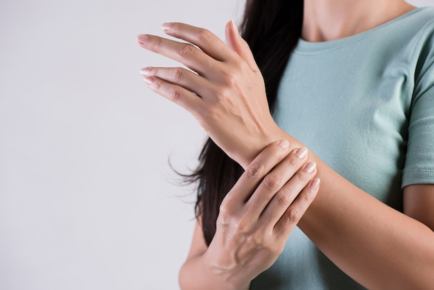 Woman holds her wrist hand injury, feeling pain.