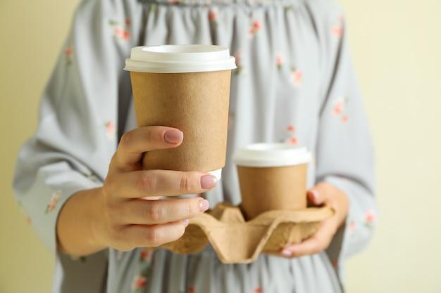 여자는 종이 커피 컵 홀더를 보유
