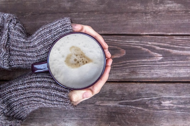 Woman holds hot cup of coffee latte, cappuccino with milk cream and heart on wooden background, top view
