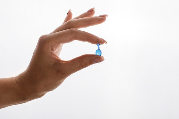 Женщина держит в руке капсулу с витаминами или маслом Бесплатные Фотографии