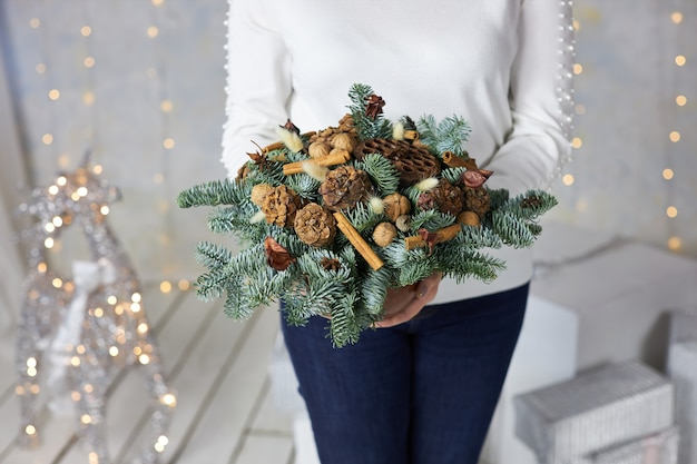 女性は彼女の手で家の装飾のための円錐形と松の枝のお祝い組成物を保持しています