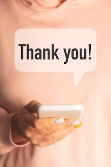 Женщина держит в руках смартфон, на который пришла благодарность. концепция дня благодарности