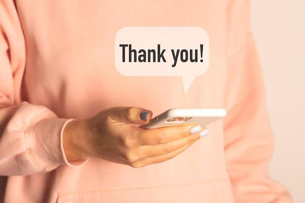 感謝のメッセージを受け取ったスマートフォンを手に持つ女性。ありがとう日のコンセプト