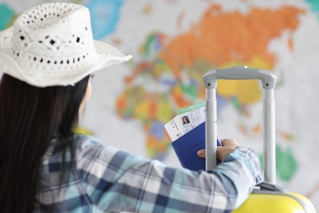 女性はコロナウイルス感染に対するワクチンのパスポートを手に持っています