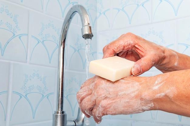 여자는 파란색 배경에 있는 금속 수도꼭지에서 물이 흐르는 비누를 손에 들고 있습니다. 바이러스성 질병 및 전염병 예방. 코로나 바이러스와 싸우고 있습니다. 물줄기에 손에 비누 바.
