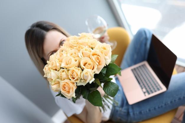 여자는 장미의 큰 꽃다발을 보유하고 그녀의 무릎에 와인 한 잔은 노트북입니다