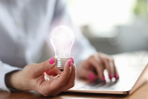 여자는 그녀의 손에 전구를 보유하고 노트북에서 작동
