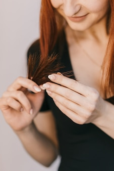 A woman holds a lock of hair in her hand and touches the tips on white.