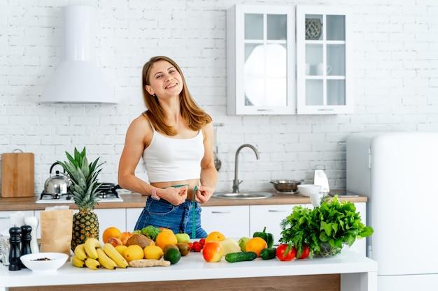 Женщина держит рулетку вокруг талии. много фруктов и овощей на столе. на диете.