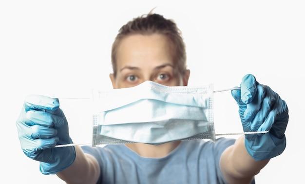 여자는 흰색 절연 얼굴 앞에서 의료 마스크를 보유